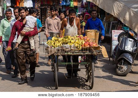 PUSHKAR INDIA - OCTOBER 28 2014: Indian man sells fruit on a cart at the during Pushkar Camel Mela