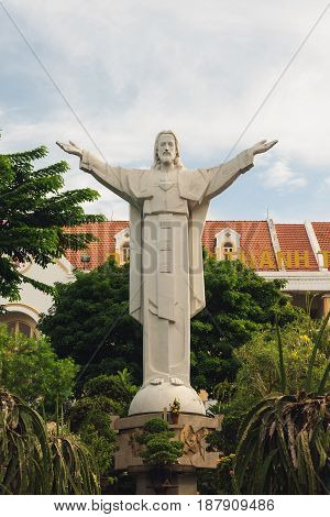Jesus Christ Statue in Hochiminh. Grey statue with open arms in the courtyard of Tan Dinh Pink Catholic Church. Ho Chi Minh city Vietnam may 2017