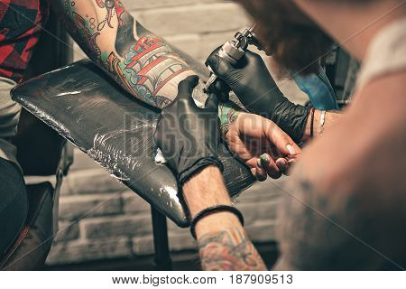 Bearded man painting image on arm of female with special equipment. He turning back to camera. Close up