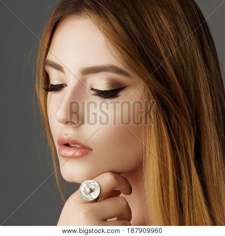 Beautiful model with long brown straight hair and ring on finger. Perfect makeup.