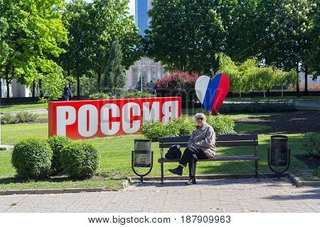 Donetsk Ukraine - May 17 2017: Woman in a park in the city center against the background of the installation with the inscription