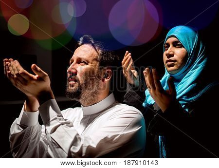 Muslim father and mother praying or god with their hands up