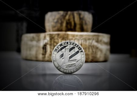 Digital currency physical silver litecoin coin near wooden ashtray
