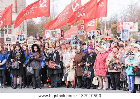 Kirishi, Russia - 9 May, Standing under red flags people, 9 May, 2017. Holding a festive rally dedicated to the Victory Day.
