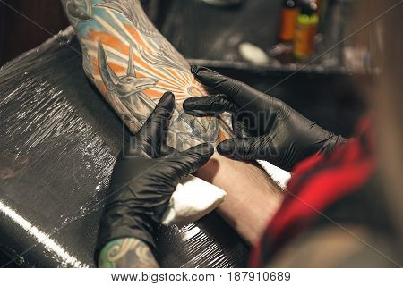 Close up of arm of male with tattoo of Anubis. Woman checking quality of painted image on arm. She turning back to camera