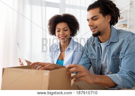 people, delivery and consumerism concept - happy couple with open parcel box and paper form home