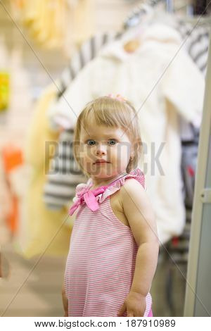 Happy little girl in the children's clothing store looking at the camera