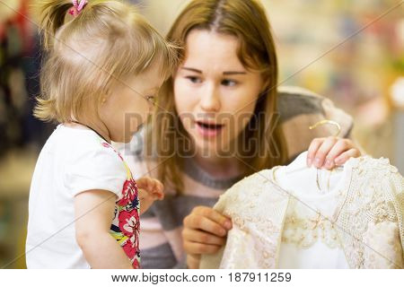A young mother chooses a dress for her little daughter in clothing store