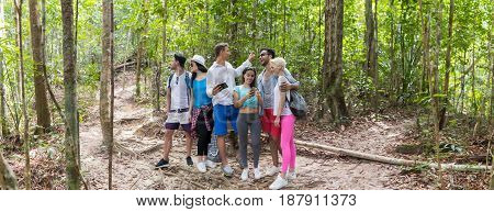 People Group With Backpacks Trekking On Forest Path Using Cell Smart Phone Map, Young Men And Woman On Hike Mix Race Tourists Hiking