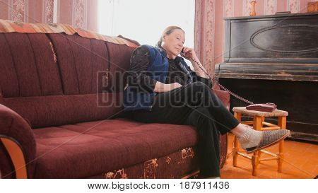 elderly woman talking on the phone in the apartment near the piano