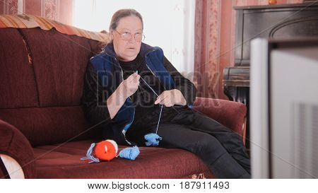 An elderly woman is knitting some socks and watching TV, old lady