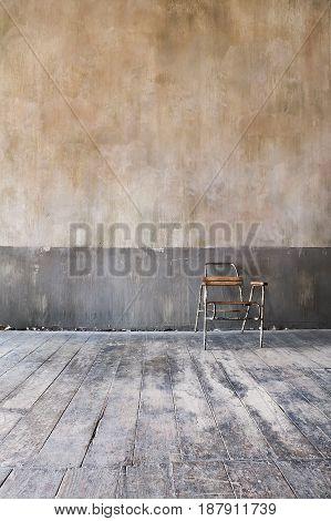 wooden chair in grungy interior. Loneliness estrangement alienation concept.