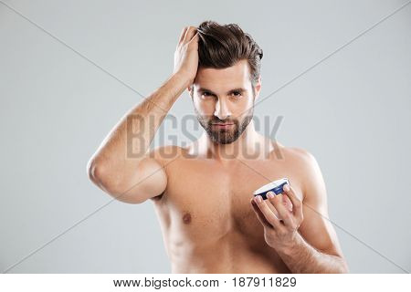 Young metrosexual man holding cream isolated over grey