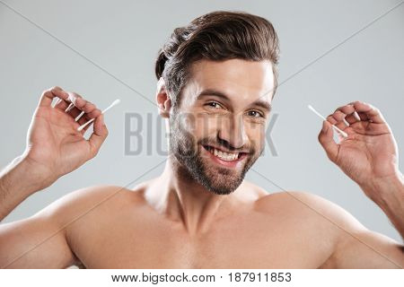 Young bearded man with ear sticks smiling to camera isolated
