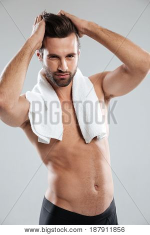 Vertical image of young bearded muscular man with towel