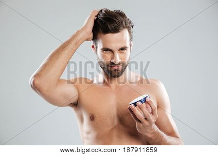Young serious man straighten hair and holding cream in hand isolated