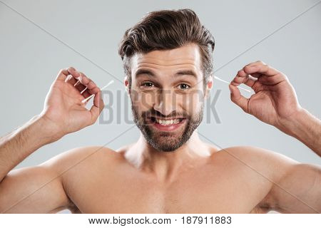 Young happy bearded man with ear sticks smiling to camera isolated