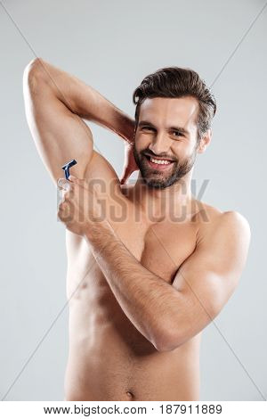 Young smiling bearded man shaving isolated over grey