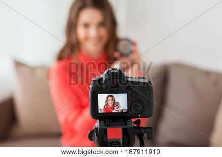 blogging, technology, videoblog, makeup and people concept - happy smiling woman or beauty blogger with bronzer, brush and camera recording tutorial video at home