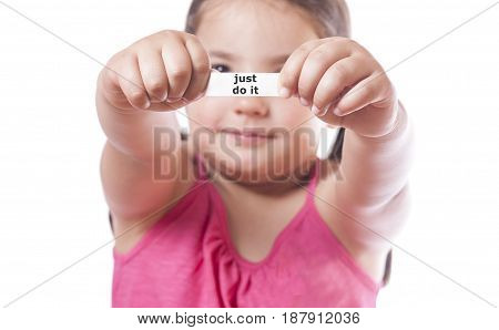 Young girl holding a fortune cookie paper with the message Just do it