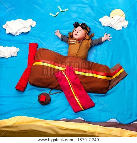 Infant baby boy wearing an aviator hat and outfit flying  against textile decoration of a blue sky with airplane