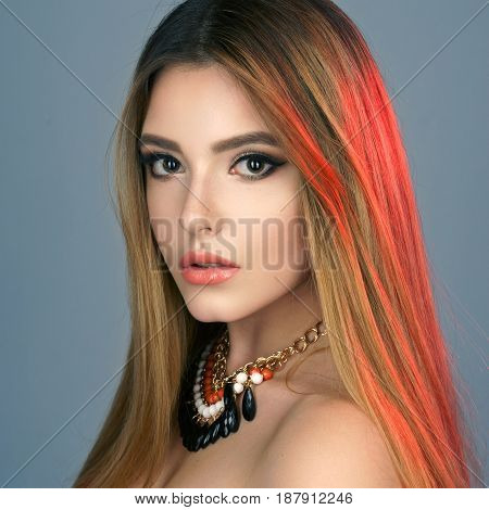 Fashion portrait of young beautiful woman with jewelry. Blonde girl with long healthy straight hair. Perfect makeup. Beauty style girl with necklace. Blue background. Red backlight.