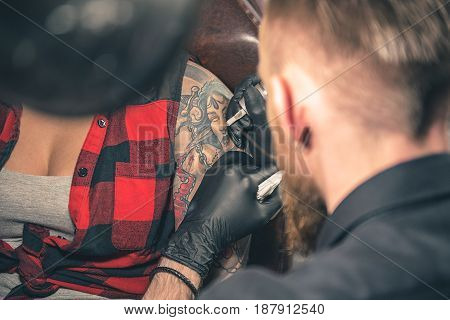 Calm man making tattoo on hand of woman. She sitting on chair