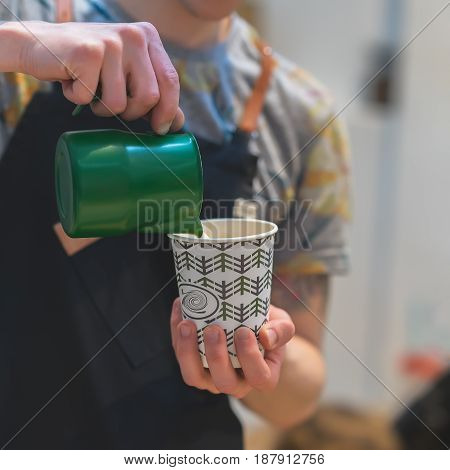 Close-up of barista hands, preparing a hot milk foam, pourin milk in paper cup with coffee cappuccino. Professional coffee making, service, catering concept
