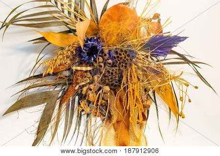 One elegant dry bouquet with various flowers hanging on the wall