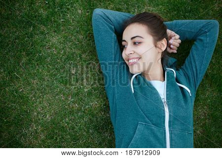 Portrait of young and sporty woman in sportswear lying on the green grass outside at the park on green meadow on cloudy day, Dnipro, Ukraine. The woman playfully smiles and laughs