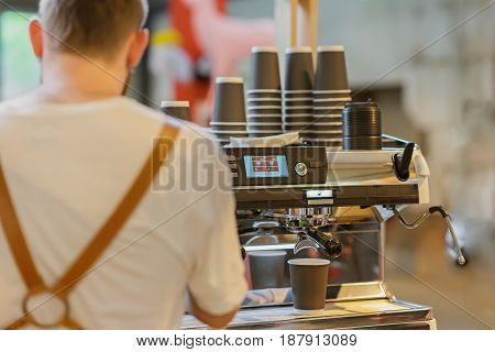 Professional barista preparing coffee in the coffee machine. View from the back. Fresh espresso. Coffee culture and professional coffee making, service and catering concepts