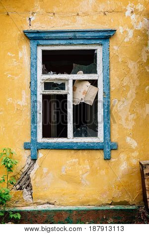 Blue broken window in old yellow abandoned house, vertical photo