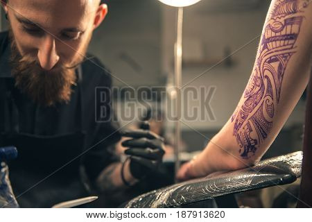 Calm bearded man creating picture on hand with special machine in salon