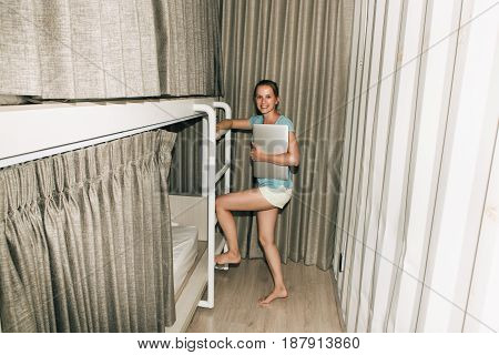 Girl standing in a stylish hostel bedroom. Young woman with laptop smiling in hotel room with two-levels beds. Evening grey curtain and wall