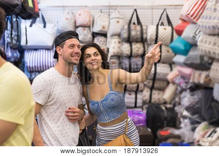 Young Couple On Shopping Choosing Bag, Man With Woman Point Finger Happy Smiling In Retail Store Selecting Female Purse