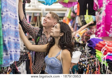 Young Couple On Shopping Choosing Clothes, Man And Woman Buyers Happy Smiling In Retail Store Selecting Dress