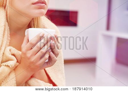 Midsection of young woman holding coffee mug in house