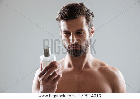 Bearded man gazing at bottle of perfume isolated