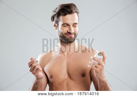 Smiling young man opening perfume in hands isolated