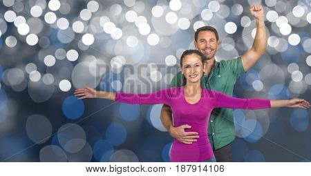 Digital composite of Smiling man and woman with arms raised over bokeh