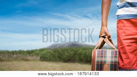 Digital composite of Cropped image of traveler carrying bag on mountain