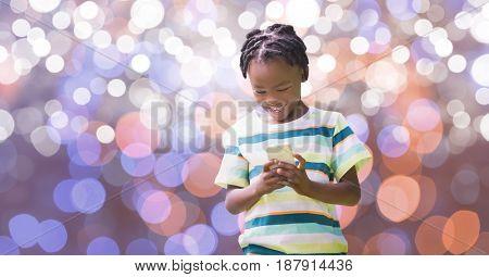 Digital composite of Happy boy using smart phone over bokeh