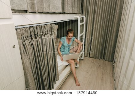 Girl standing in a stylish hostel bedroom. Young woman working on laptop in hotel room with two-levels beds. Evening grey curtain and wall