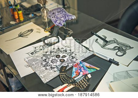Top view of sketches of tattoo and different tools situating on table in apartment. Close up