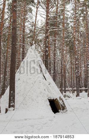 Winter, day. In the frame primitive housing of primitive man - yurt. Tomskaya pisanitsa, museum, reserve. Kemerovo, Siberia, Russia.