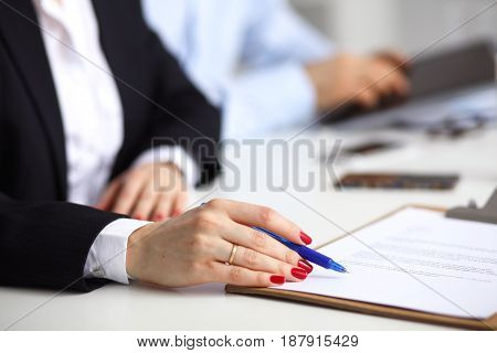 Young businesswoman sitting on the desk with folder, contract .