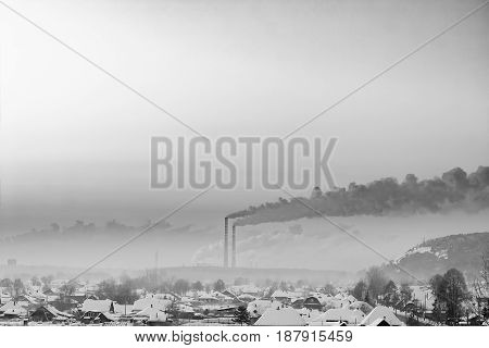 Winter snow. Early morning. Dense smoke pollutes the air. Kemerovo. Siberia. Russia. Black and white image.