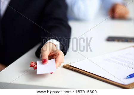 Female hand holding a blank business card sitting on the desk, selective focus.