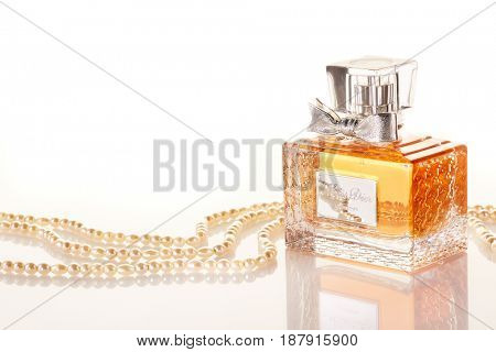 St.Petersburg, Russia - May 2017 - Christian Dior bottle of perfume and pearls on a white background with reflection.