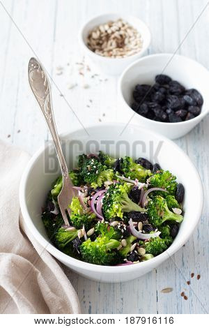 Broccoli with raisins red onions and seeds. Healthy raw diet salad. In a white bowl on a blue wooden background. Selective focus